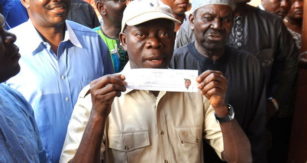 EDO STATE GOVERNOR ADAMS OSHIOMHOLE DISPLAYING HIS ALL PROGRESSIVES CONGRESS (APC) MEMBERSHIP CARD AFTER REGISTERING AT IYAMHO, ETSAKO WEST LOCAL GOVERNMENT AREA.