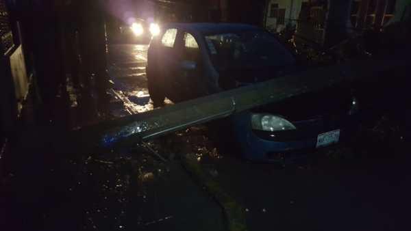 Cae poste de concreto sobre vehículo
