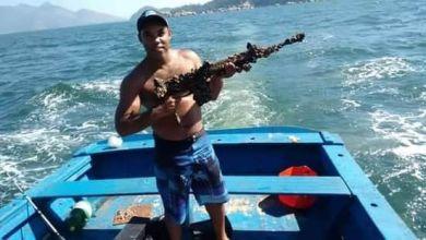 Foto de Foto de pescador exibindo fuzil achado no mar viraliza