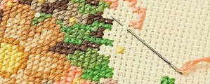 Closeup of needle put into cross-stitch embroidery.