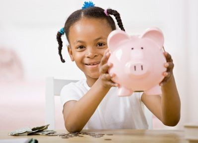 Responsible girl putting money into piggy bank for future saving