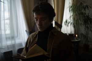 man in brown jacket reading book
