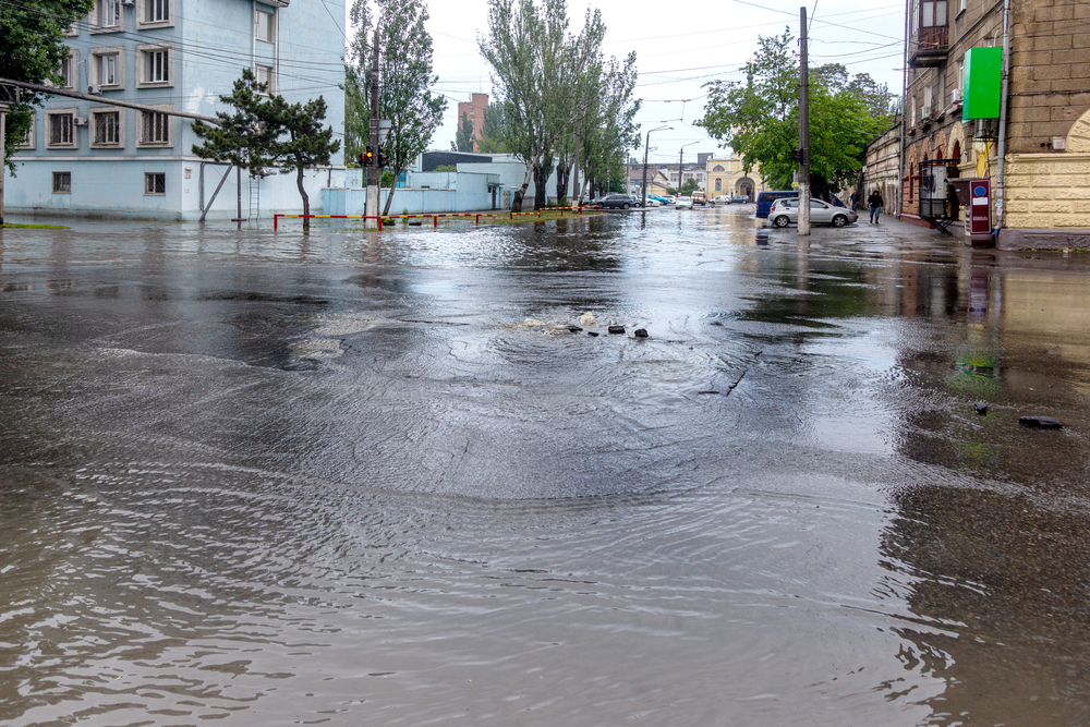 Flooding after heavy rains in city. Sewage broke open asphalt and blew up fountain. Dirty sewage broke through storm sewer and spilled onto streets of city after rain. Danger of epidemic and infection
