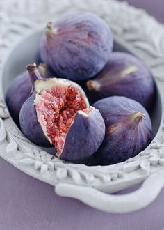Bowl of fresh figs, one broken open to show red flesh.