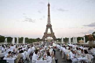 Participants dressed in white take part in Diner en Blanc, or White Dinner at the Trocadero gardens in front the Eiffel Tower in Paris, Thursday, June 13, 2013. The event is a reminiscent of flash mobs, where hundreds of people descend on one area at a specific time, summoned by SMS text message, gsm phone call or email. (AP Photo/Thibault Camus)