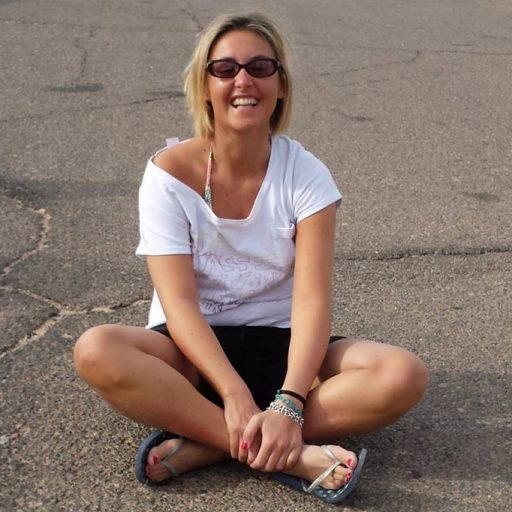 io,l'Ingegnererrante, seduta per terra su una strada e sorridente