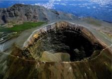Veduta aerea del Gran Cono del Vesuvio. Sullo sfondo: la parete interna della caldera del M. Somma e il territorio vesuviano parzialmente urbanizzato