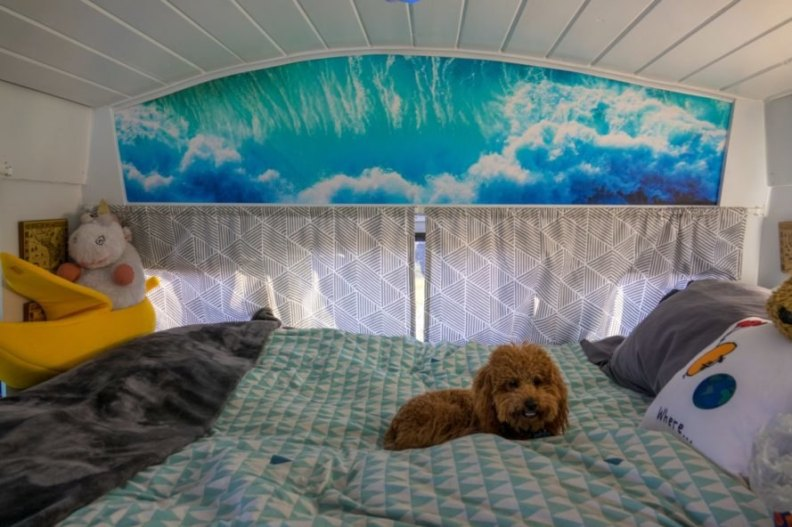 small bedroom with cute little doggie on the bed