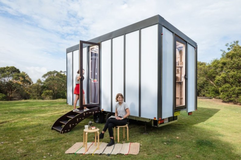 white tiny home with person sitting outside in a chair