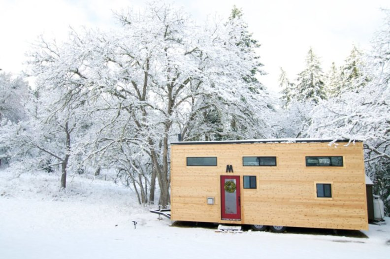 wooden tiny home with windows in snowy landscape