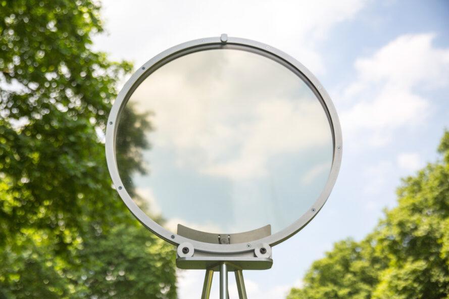 circular smog tracker device near lake with transparent center