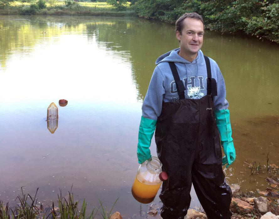 Riefler holding jug of polluted water while standing next to a stream