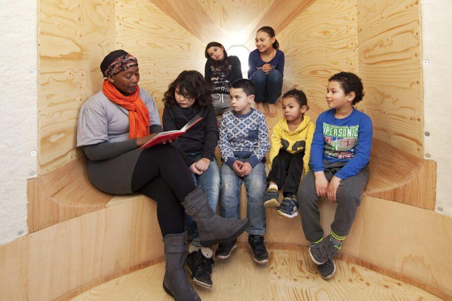 kids listening to person reading from a book