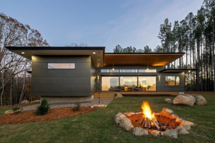 A backyard with grass and a firepit behind the house.