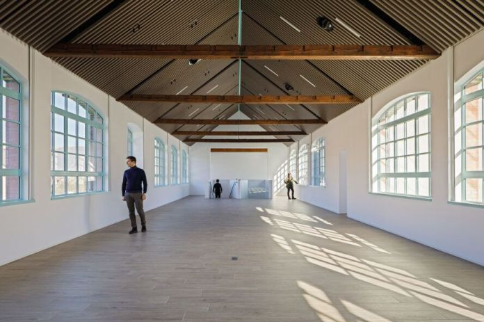 long white room with pitched ceiling and exposed structural beams