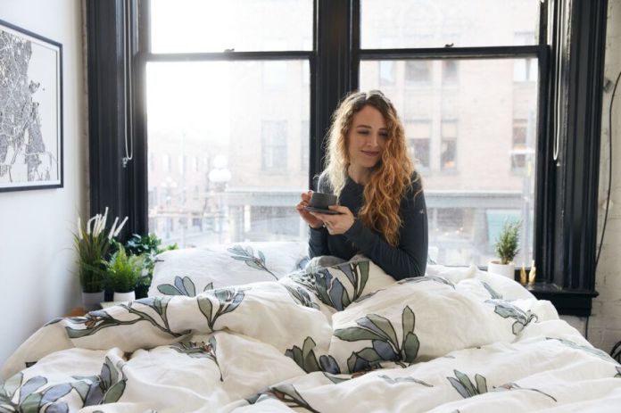 person holding mug and sitting in bed