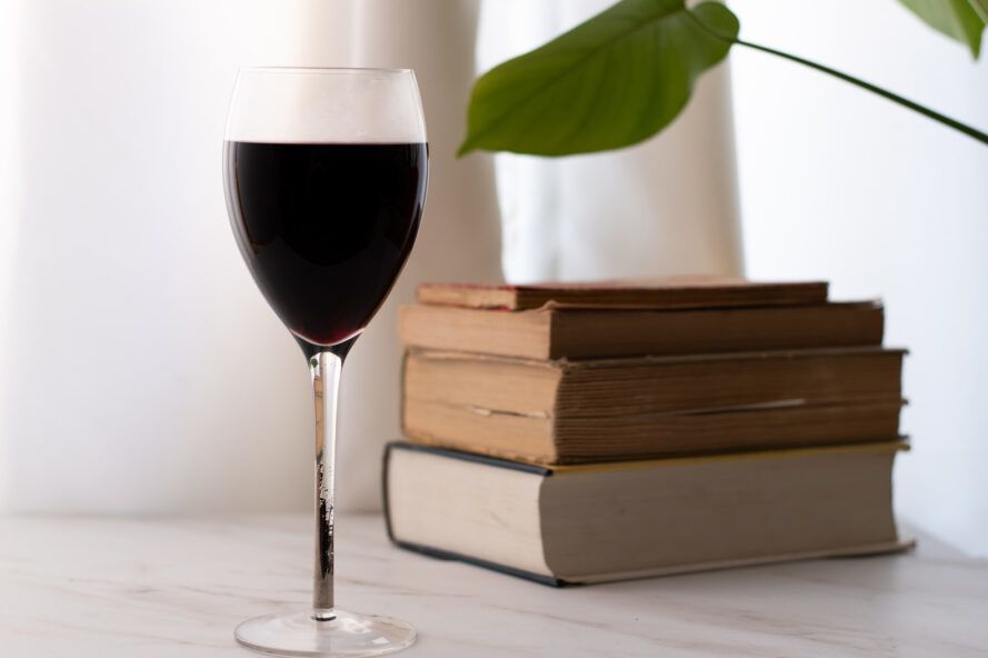 glass of wine by pile of books