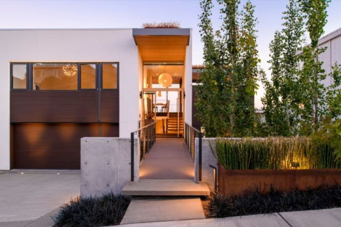 A rectangular home with a garage to the left and a walkway toward the front door at the center of the image. To the right are green plants.
