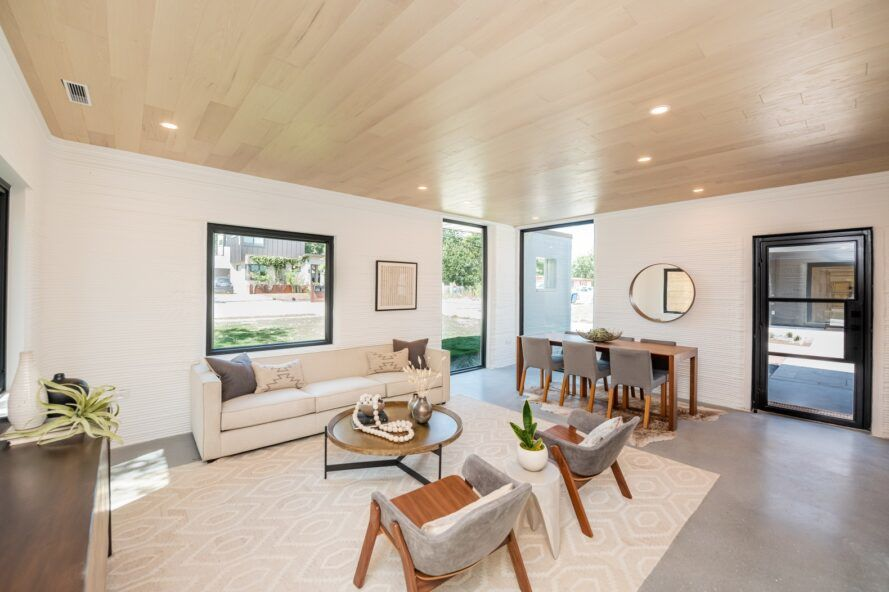A neutral living area with white walls, a white rug, wood ceilings, a white sofa and gray chairs.