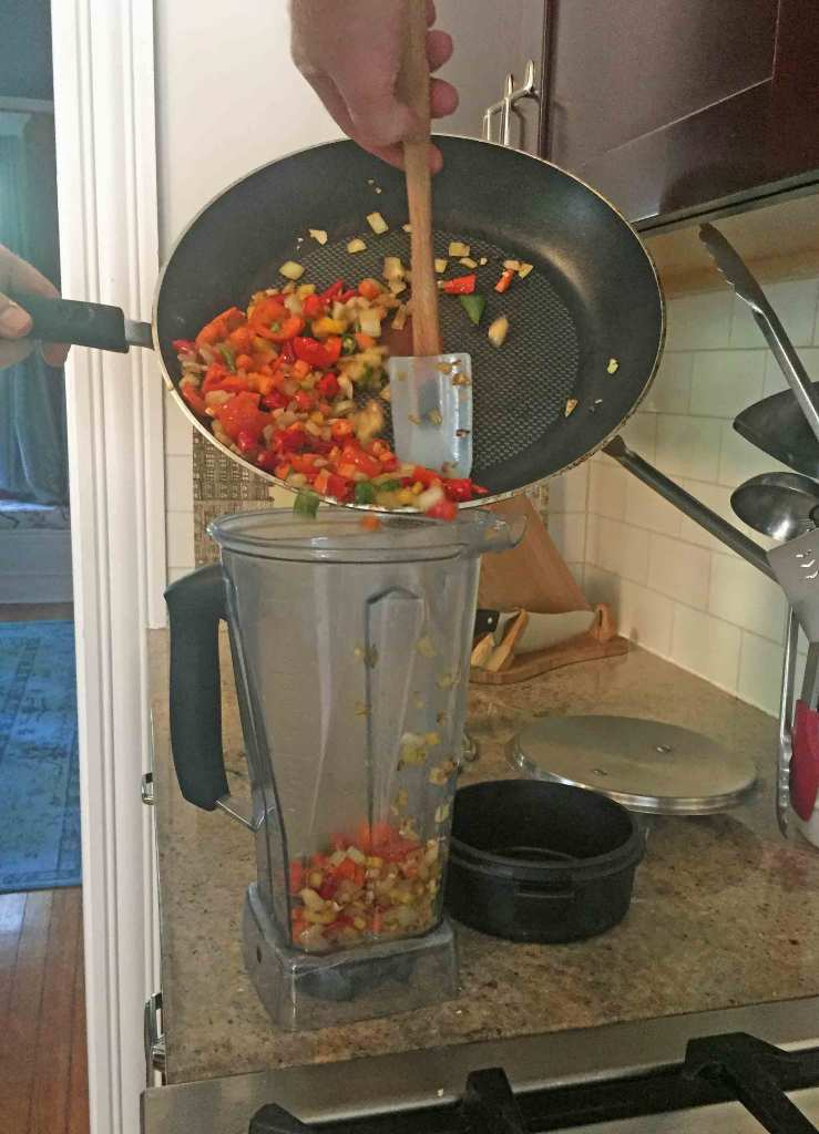 Pour sauted vegetables into the blender. Add the bourbon and apple cider vinegar for the Old Grand-Dad Kentucky Hot Sauce.