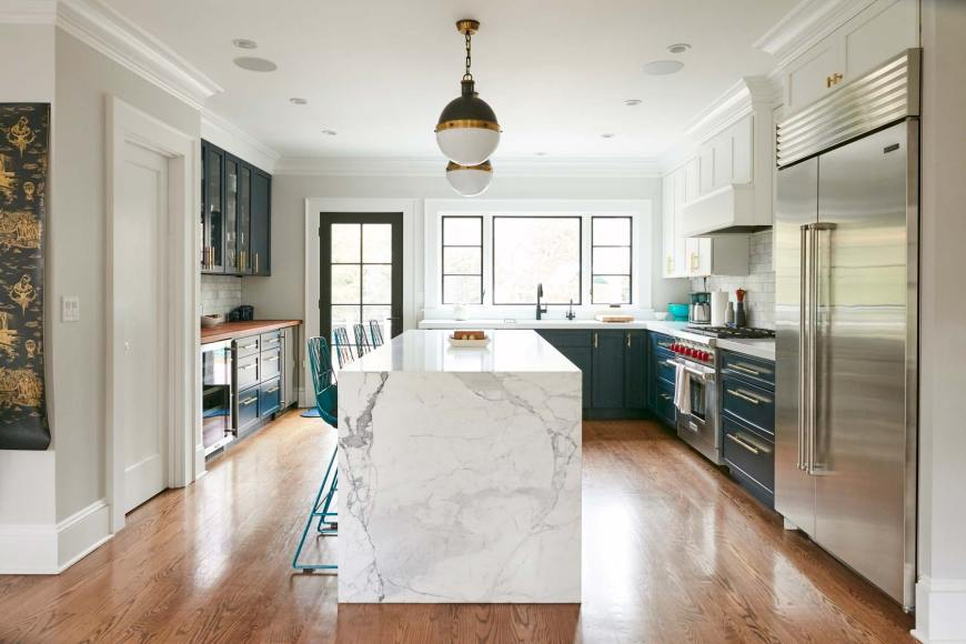 Kitchen cabinets in rich navy contrasted with a beautifully veined slab of marble. SNEAK PEEK! Seeing her home as an ever-evolving piece of art, check out the wallpaper sample to the left. It was designed by Mike D. Yes, that Mike D.