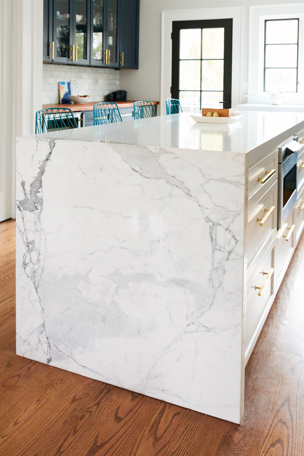A waterfall feature made from a slab of marble mitered with several smaller pieces gives the illusion of thickness.