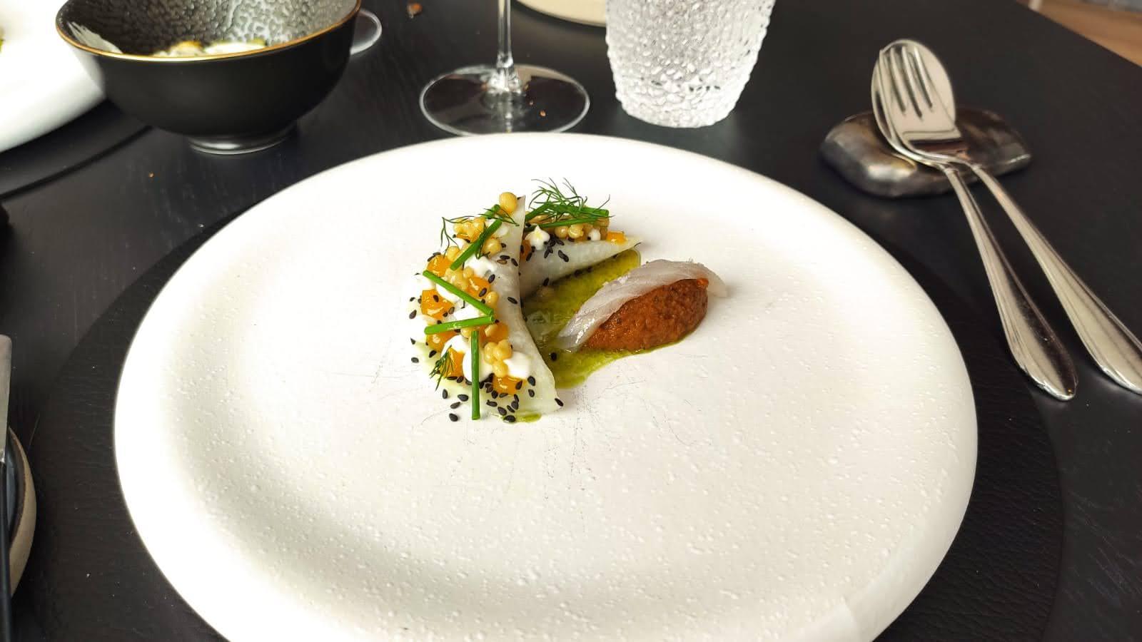 Ravioli van koolrabi met ceviche van zeebaars, crème van citroen, garum (Latijnse vissaus), kaviaar van olijf en tartaar van aubergine