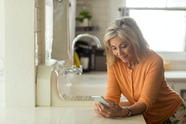 Woman shopping for prescriptions with online pharmacy on her phone in her kitchen