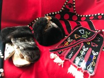 "Some of Lisa's artwork. From left to right: seal skin mittens, otter skin hat, ""octopus"" bag. Behind, a button blanket displays a porpoise, a crest of the Chookaneidi Tlingit."