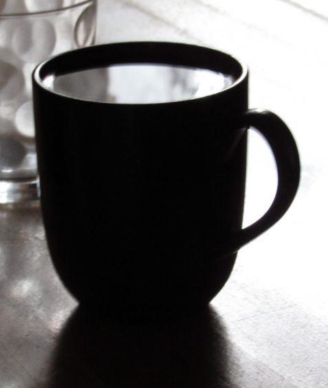 Photo of filled coffee cup reflecting white light