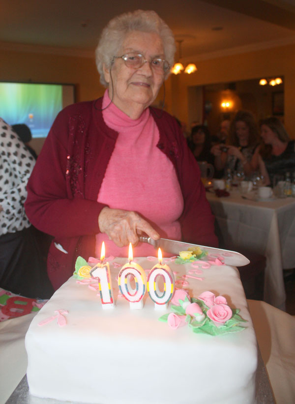 Mary McCloskey cutting the cake to celebrate her 100th birthday.