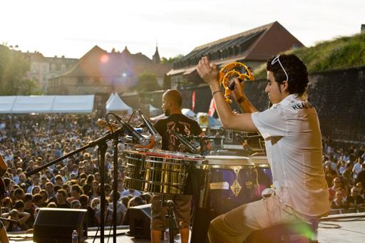 Mise en valeur de la prestation du groupe de musique en montrant la taille de la foule assistant au spectacle.