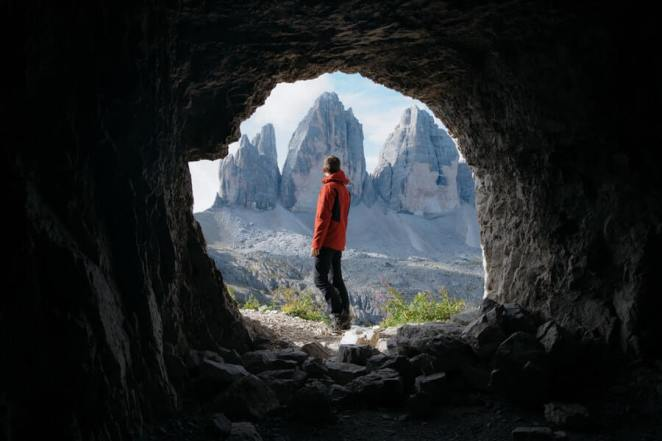 Man Outside cave in Front of 3 Mountains