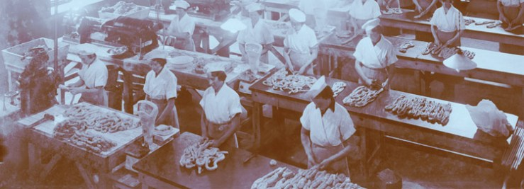 Women in uniforms standing at long tables, handling sausages.