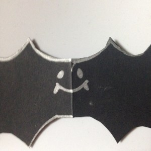 Halloween Candy Catcher, black construction paper, silver gel pen outline of bat, cut out, with smiley face.