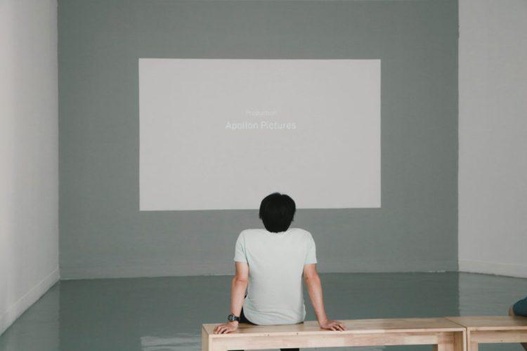 Mann auf Bank in einem fast kahlen Raum sieht auf eine große fast leere Projektionsfläche. Dort steht
