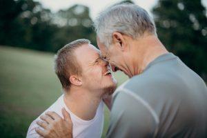 Zwei Männer stehen Nase an Nas eund lachen, der linke ist etwas kleiner und jünger, der rechte Mann hat dem linken Mann seine Hände auf die Schultern gelegt. Der linke Mann hat Down Syndrom. Im Hintergrund ist Rasen zu sehen, der von Büschen umrandet ist.