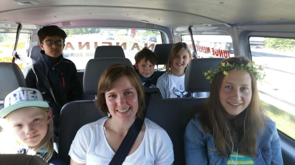 Blick in den Innenraum eines Kleinbusses, in dem lächelnde Kinder sitzen. Vorne rechts sitzt ein Mädchen mit Blumenkranz im Haar.