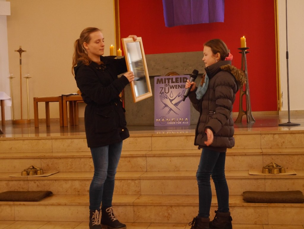 Zwei Mädchen im Altarraum einer Kirche. Die eine spricht in ein Mikrofon, die andere hält ihr einen Spiegel entgegen.