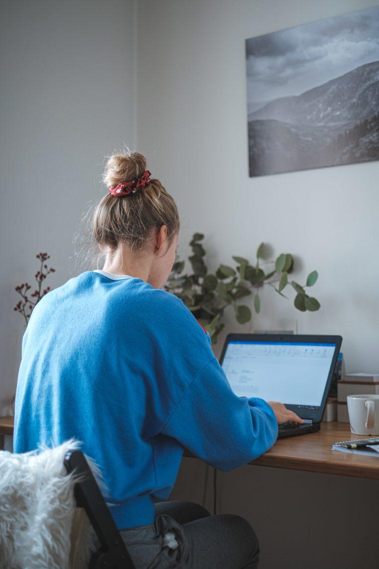 Poster mit Blick auf eine Berglandschaft an der Wand. En Tisch mit Laptop. Eine Frau sitzt davor. Man sieht sie von hinten. Rechts neben dem Laptop steht eine Kaffeetasse. Die Frau tippt.