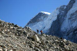Geröllfeld, am Horizont 2 Menschen, im Hintergrund ein riesiges Bergmassiv