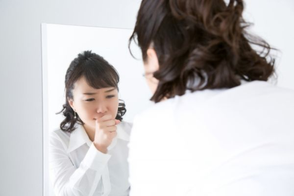 防水スプレーの噴出した有毒成分を吸い込んで体調不良になる女性