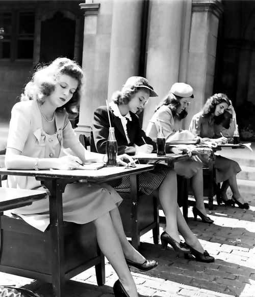 A group of 1940s female students doing their schoolwork while drinking some Coca Cola