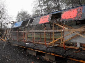 Iron ribs have been attached to the new wooden base, the cabin is supported in place...