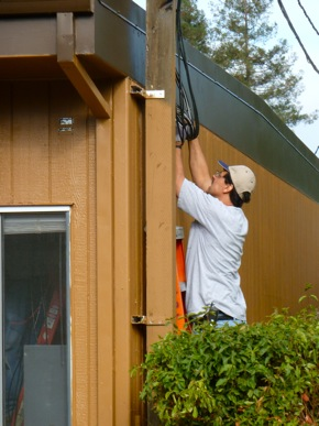 Worker at Hillview School applies wiring to portable classroom