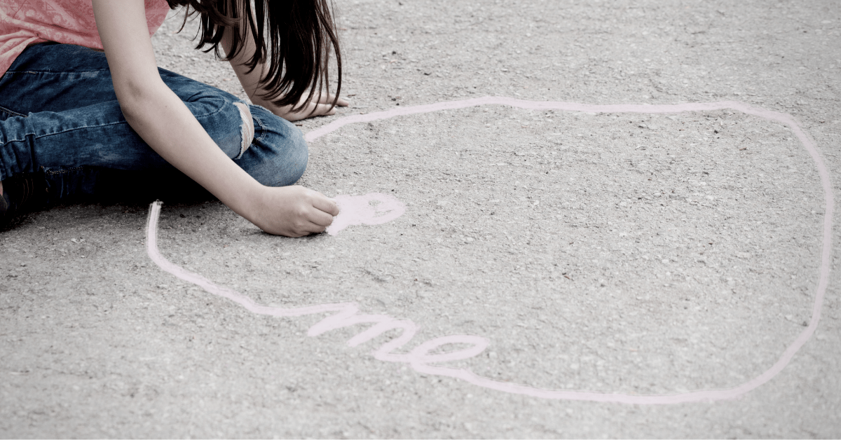 """A little girl drawing a chalk circle that says """"me"""""""
