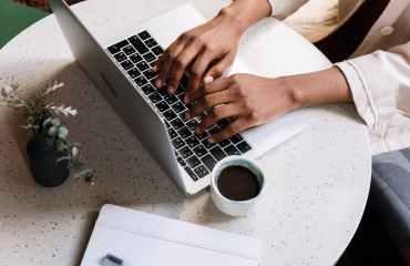 person using macbook pro beside white ceramic mug