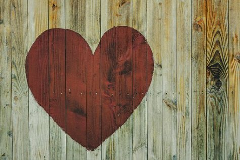red heart painted on wooden fence to symbolize trauma healing work