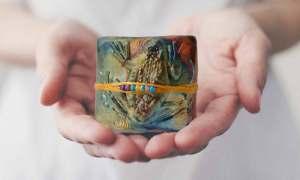 Woman holding a frog design innerSpirit Rattle