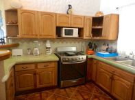 Fully equipped kitchen with custom hardwood cabinets, six burner gas stove with oven, microwave and double sink.